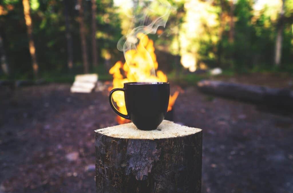 Eine Tasse Kaffee vor einem Lagerfeuer